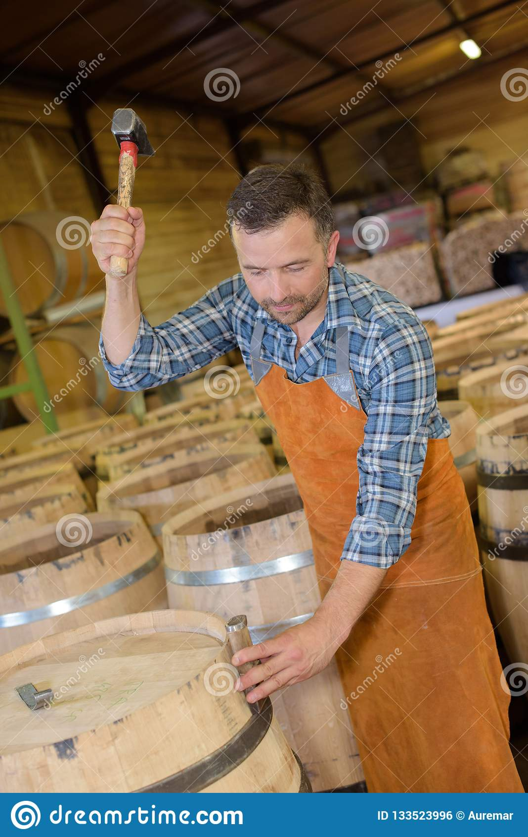 木头滚磨使用锤子和工具的生产木桶匠在车间