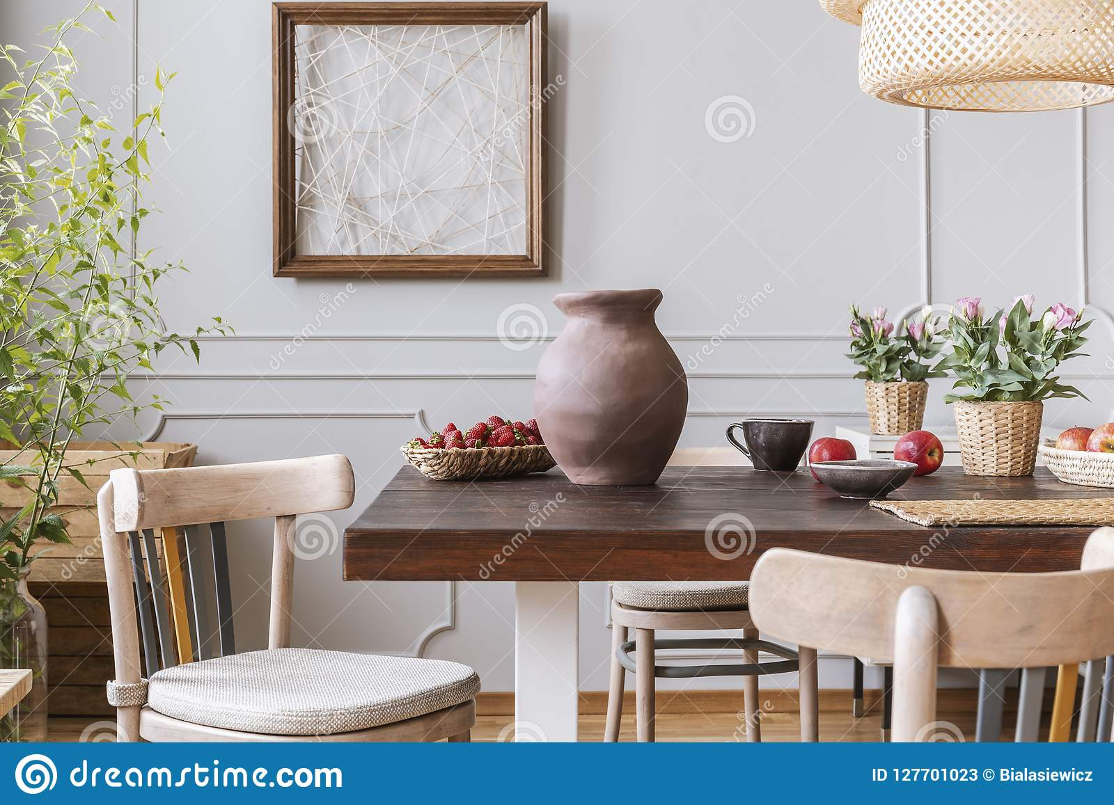 木椅子在与花瓶和花的桌上在与海报的灰色餐厅内部 实际照片