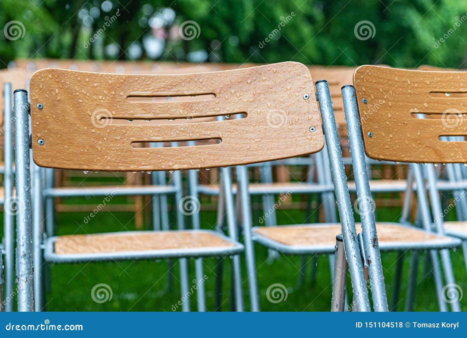 木椅子在雨中站立外部在公园 空的观众席,绿草,waterdrops,特写镜头