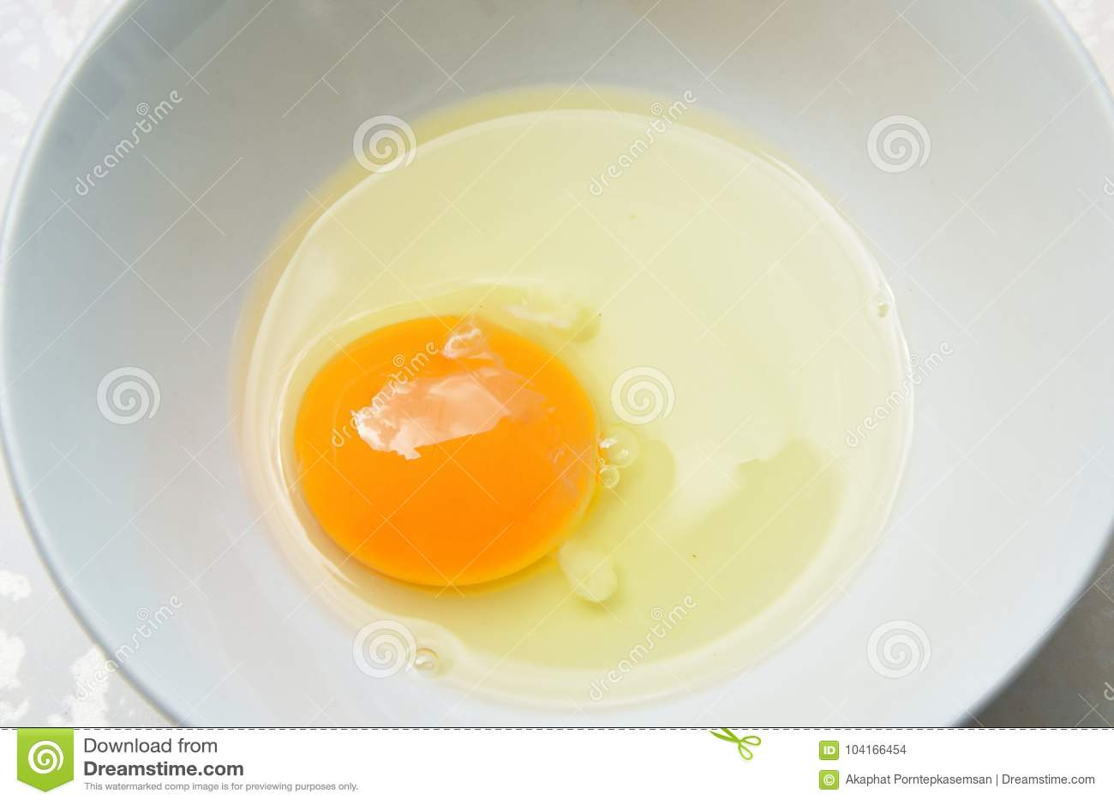 未加工的卵黄质和白鸡蛋从在杯子的壳崩裂了