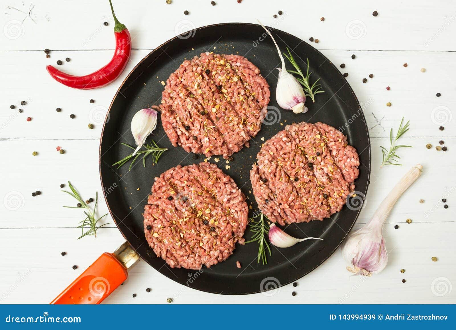 未加工的汉堡包-从有机肉的肉末用大蒜、辣椒和迷迭香在一个煎锅在白色