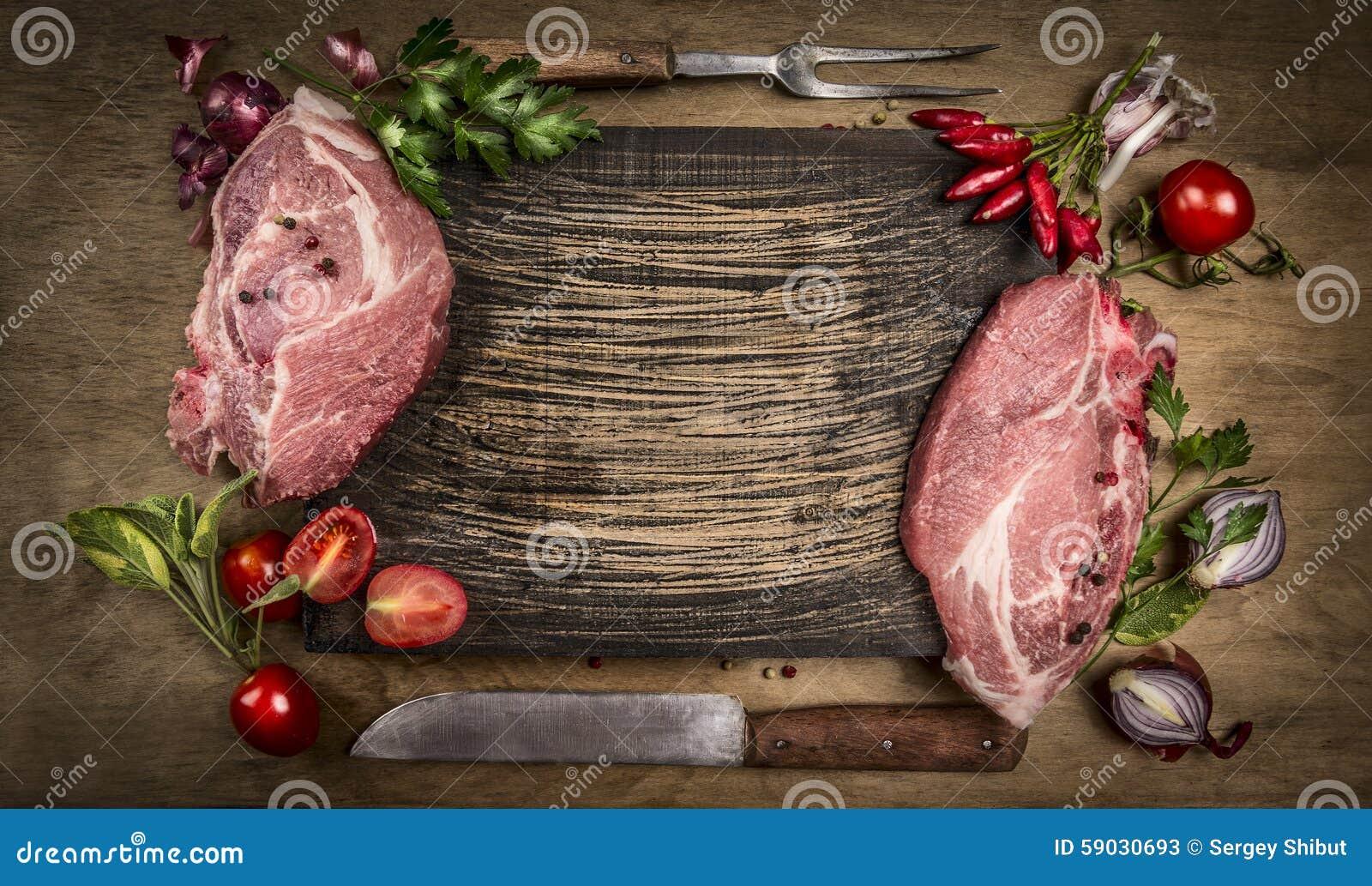 未加工的猪肉用厨房工具、新调味料和成份砍烹调的在土气木背景,顶视图,框架