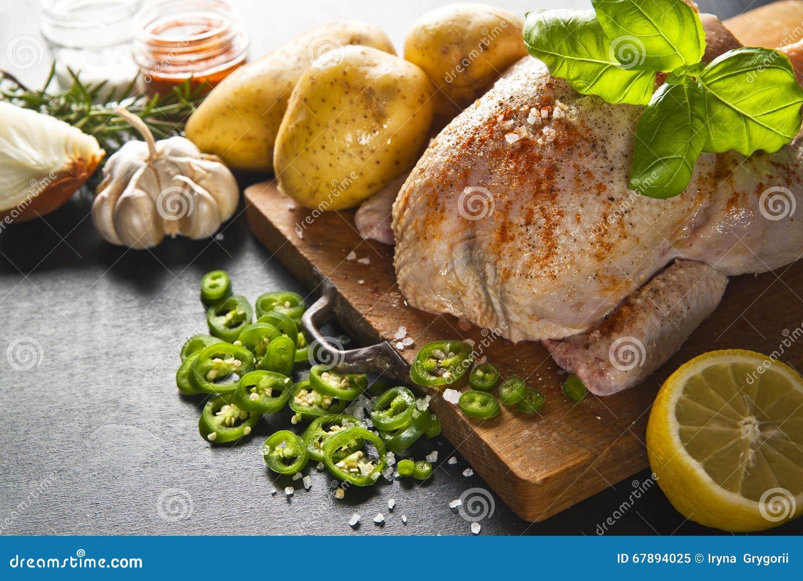 未加工的整鸡用大蒜土豆用草本准备好roas