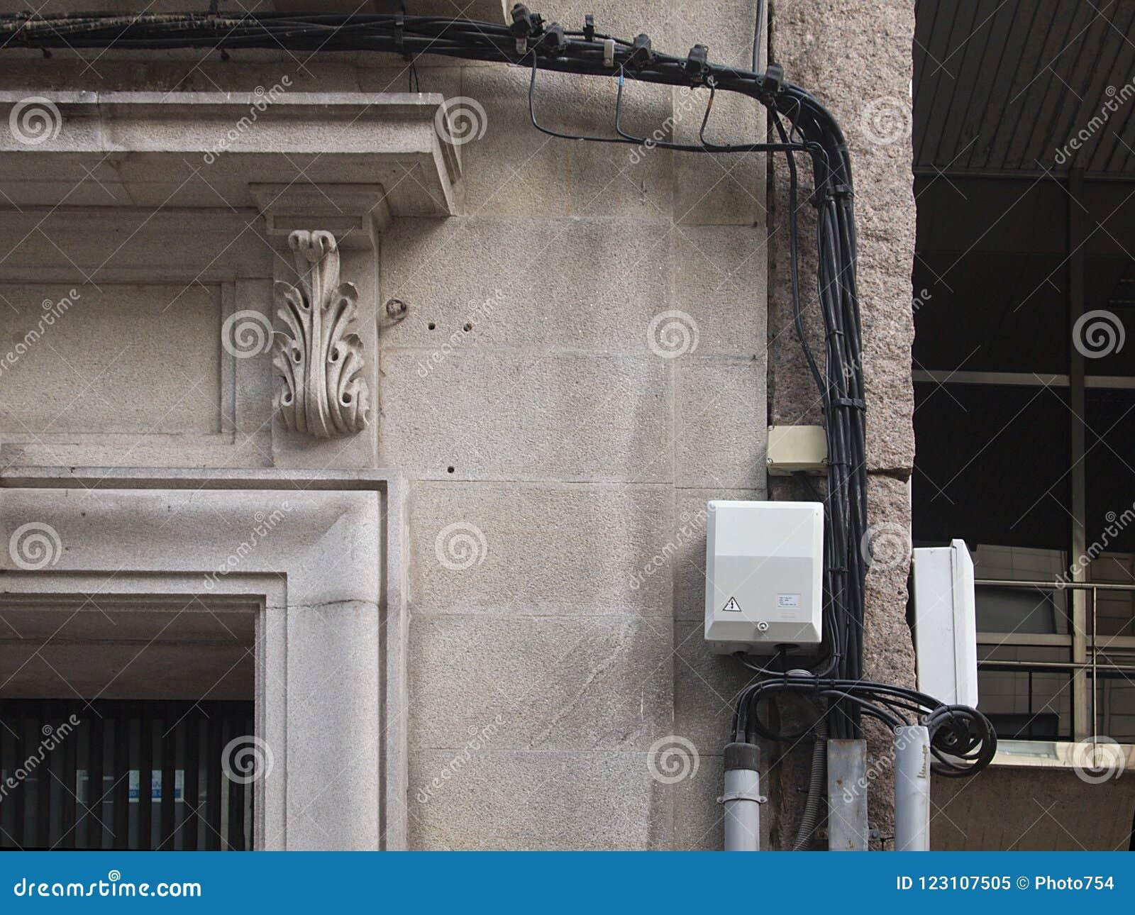 杂乱电话或电缆绳在一个石墙上垂悬了