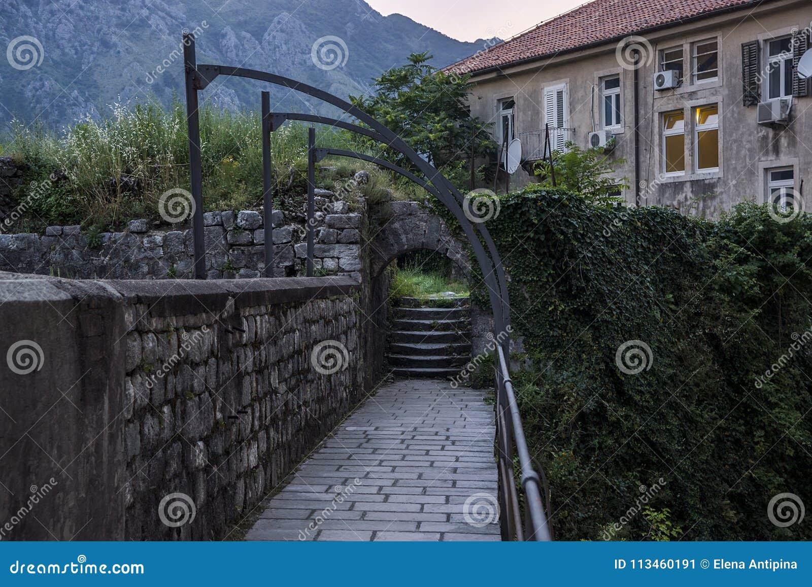 村庄的晚上视图,梯子被缠绕标尺和篱芭的,石墙 以高山为背景