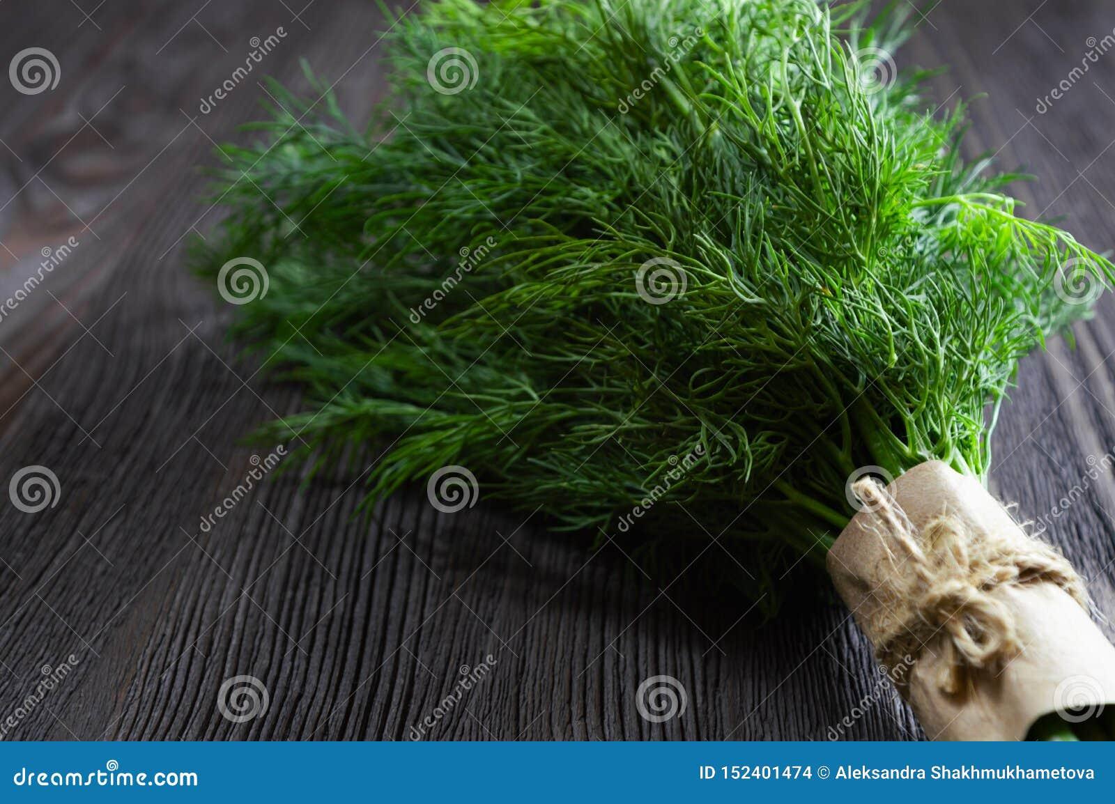 束新鲜的莳萝和香料在黑暗的木背景