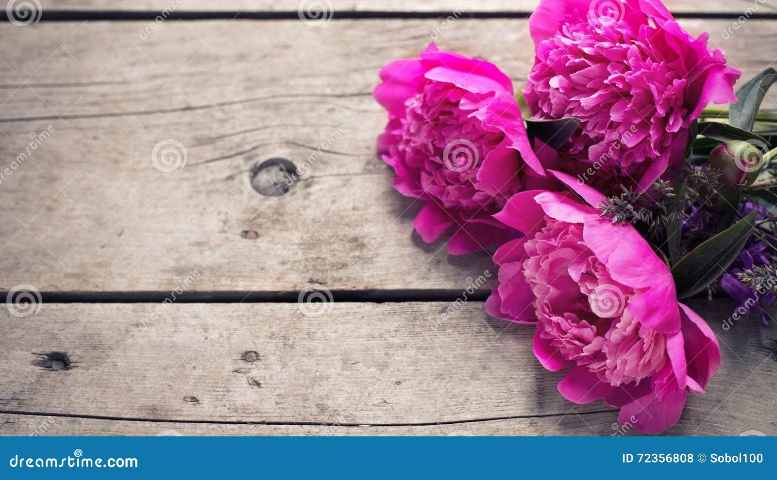 束桃红色牡丹在年迈的木背景开花