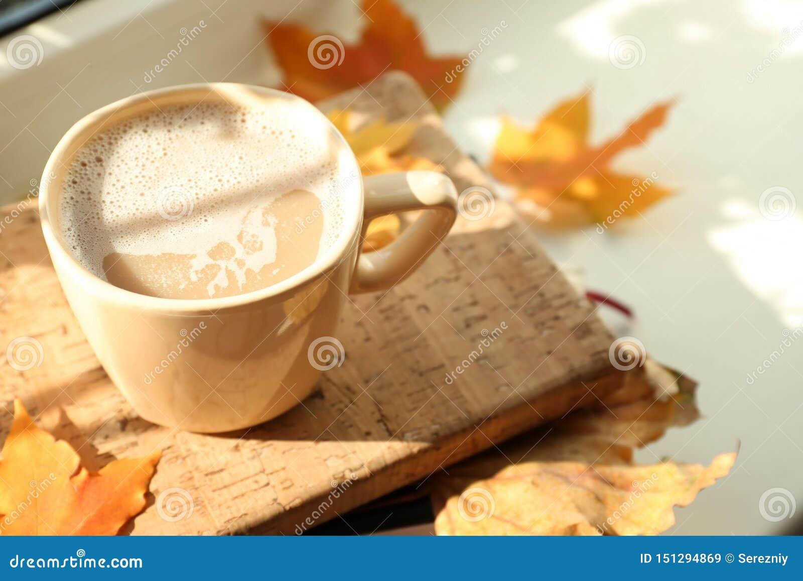 杯与书的热的咖啡和在窗台,特写镜头的秋叶