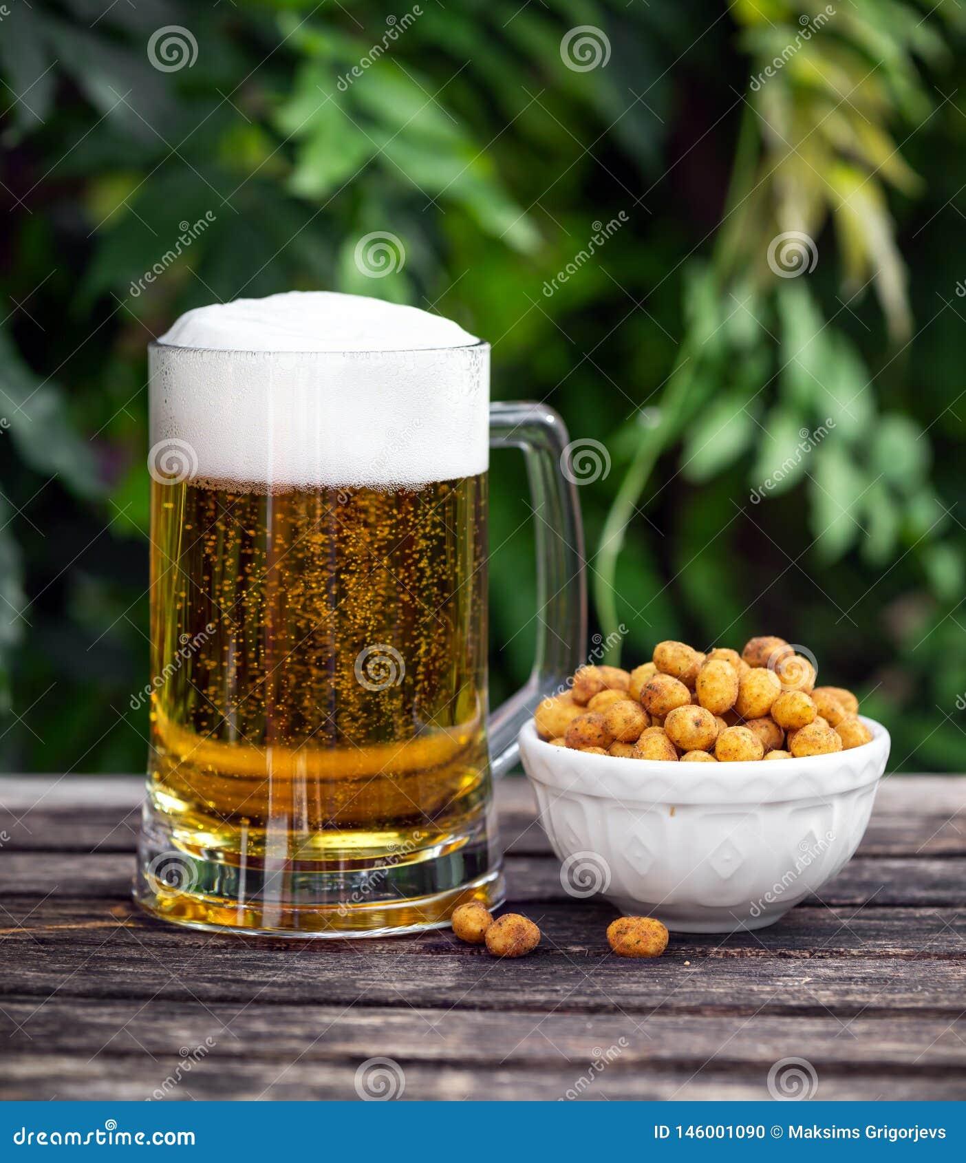 杯与快餐,在木桌上的上漆的花生的冰镇啤酒在庭院里