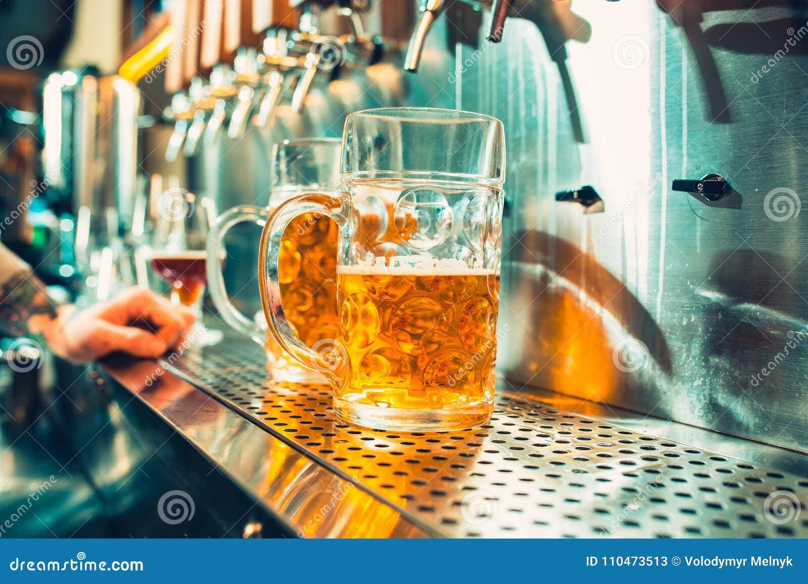 杯与桶、瓶和新鲜的蛇麻草静物画的啤酒