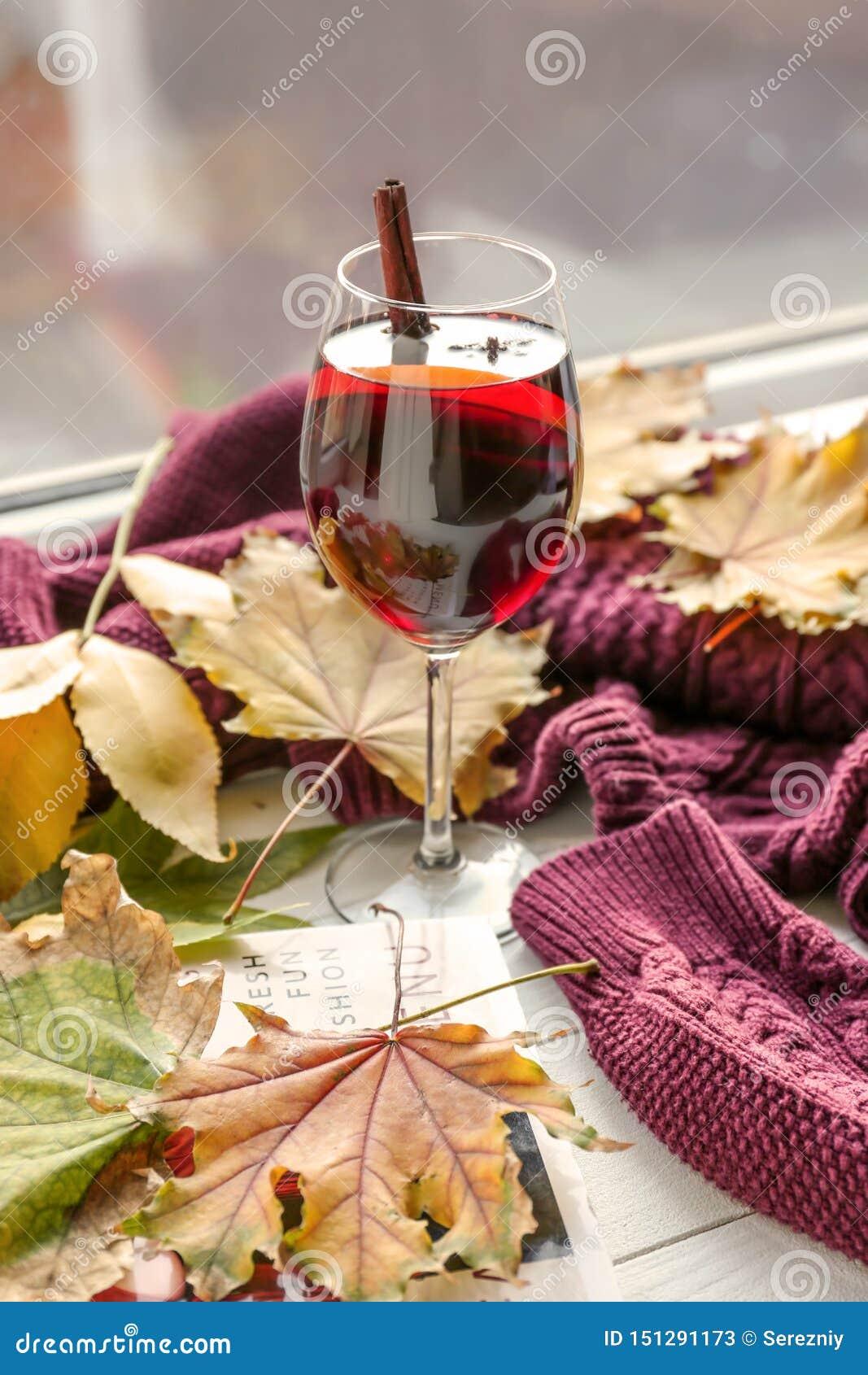 杯与秋叶的可口加香料的热葡萄酒和在木窗台的温暖的毛线衣