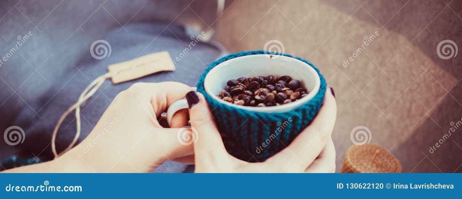 杯咖啡豆,手和温暖的毛衣,装饰用被带领的光,顶视图点