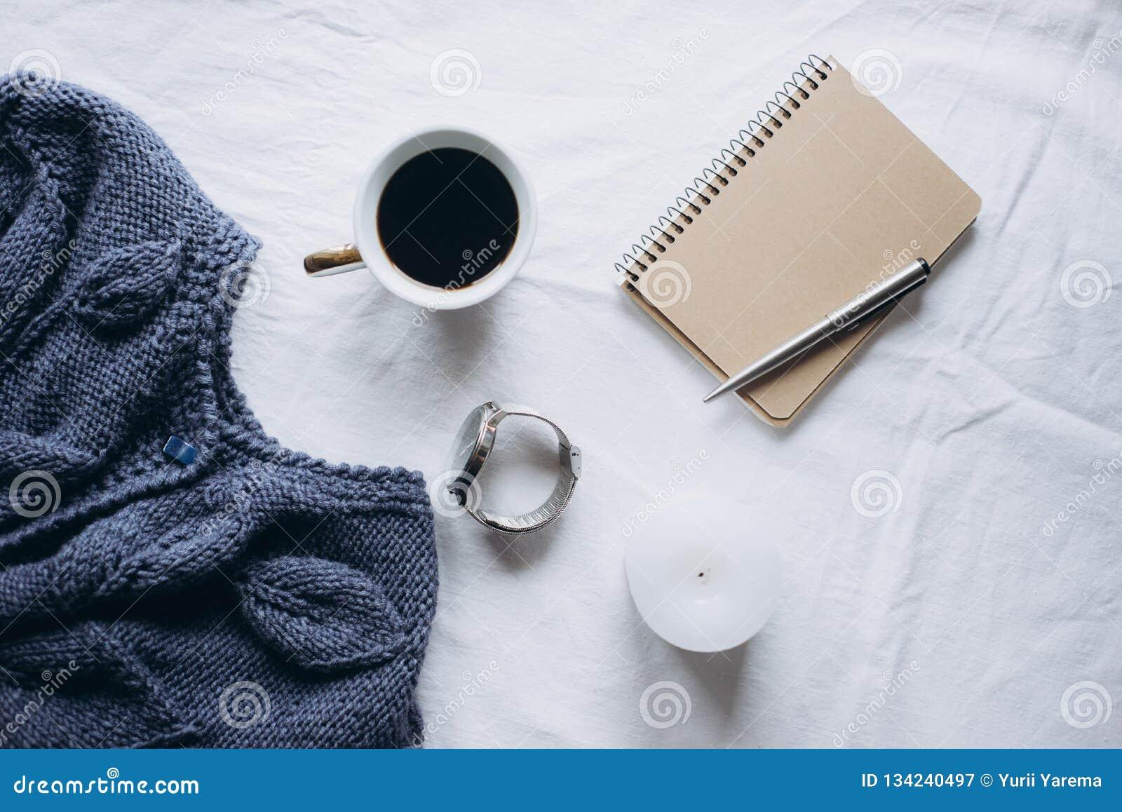 杯咖啡,蓝色被编织的毛线衣,有笔的,时钟,在床上的蜡烛,顶视图笔记本