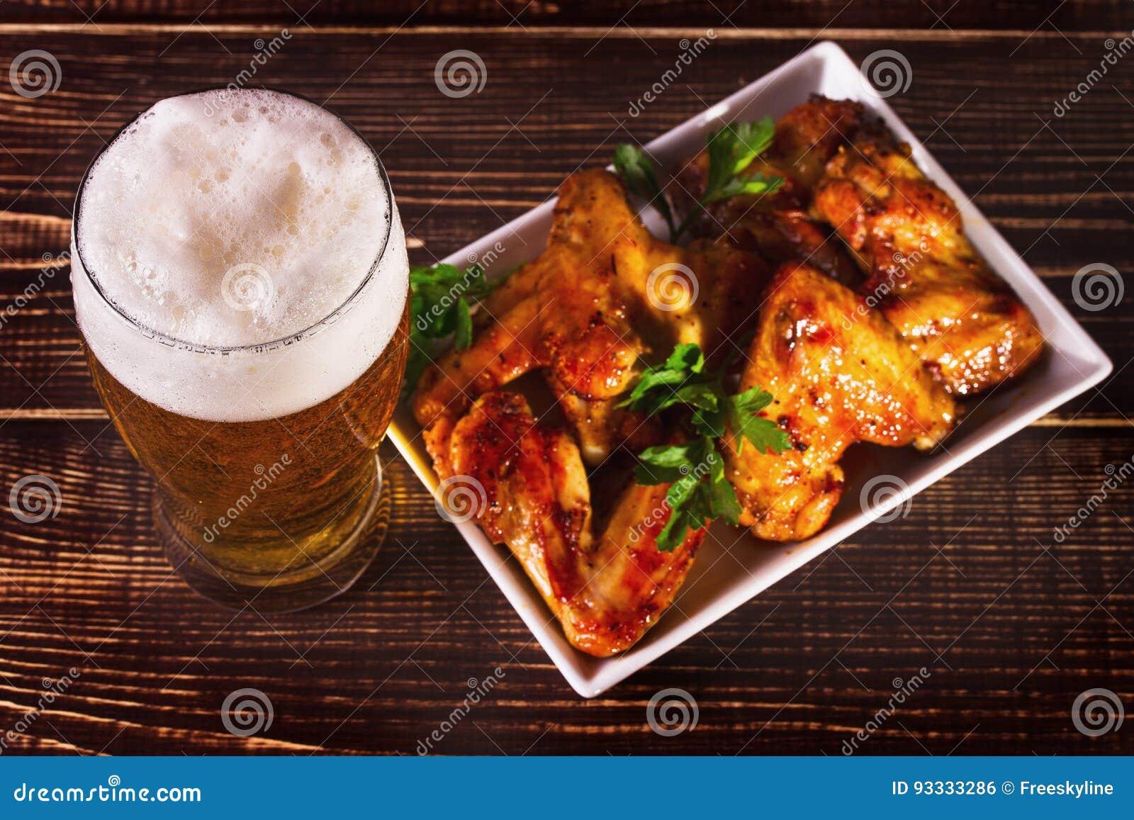 杯啤酒和水牛鸡翼 啤酒叮咬