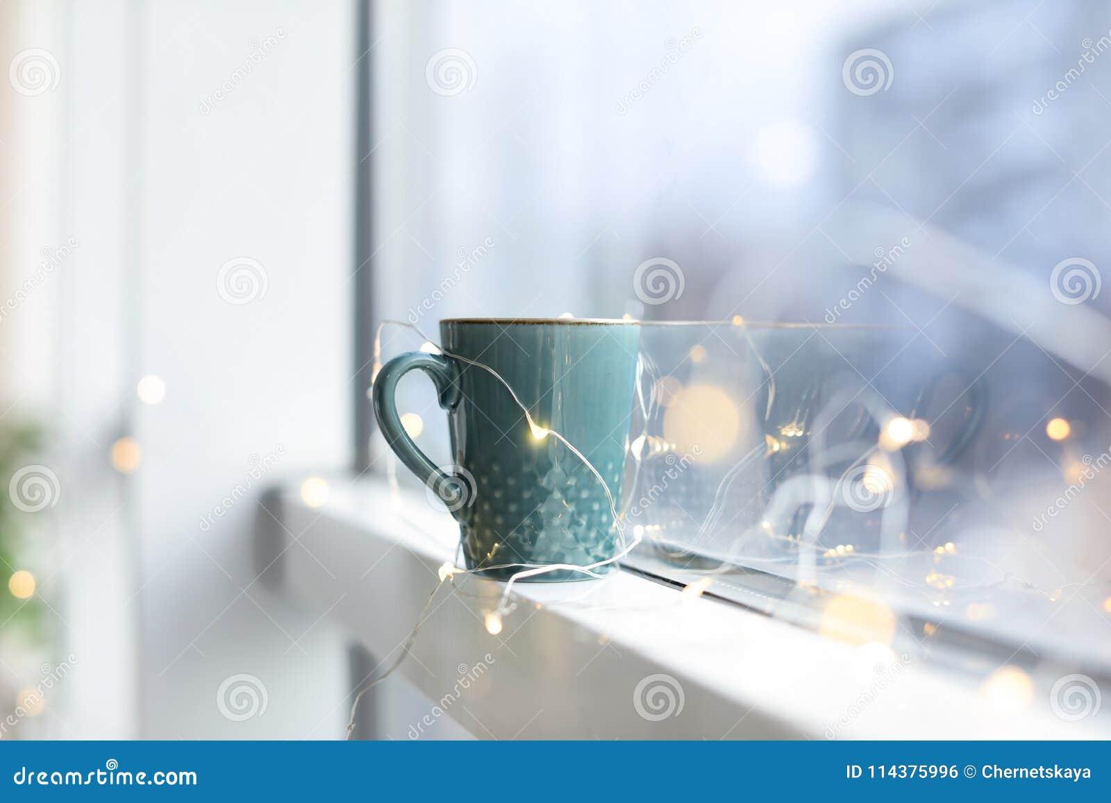 杯在窗口附近的热的咖啡