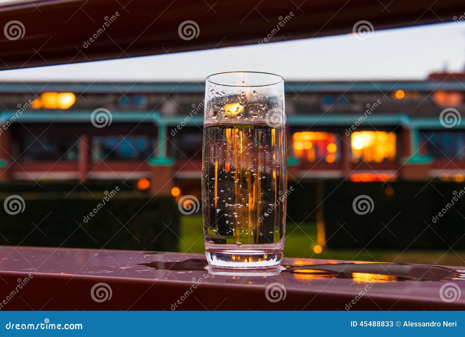 杯在阳台的水与晚上点燃背景