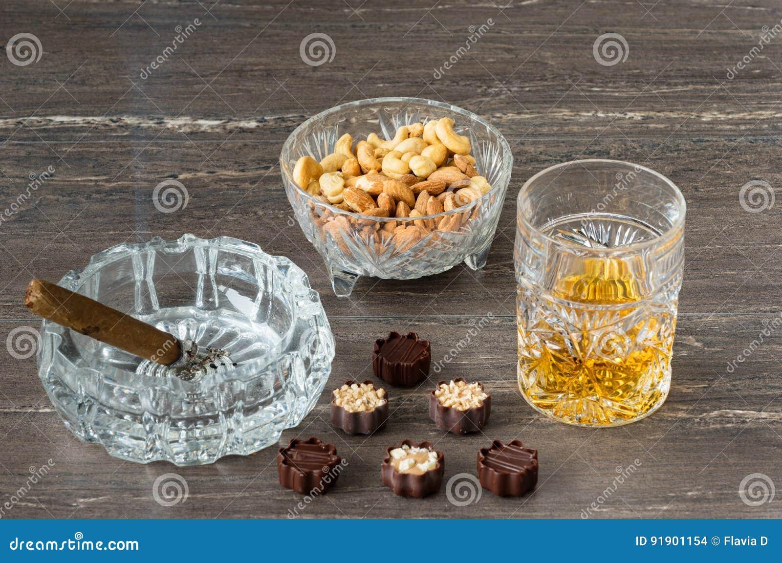 杯威士忌酒、古巴雪茄、坚果和巧克力在一张灰色木桌上 关闭上色百合软的查阅水