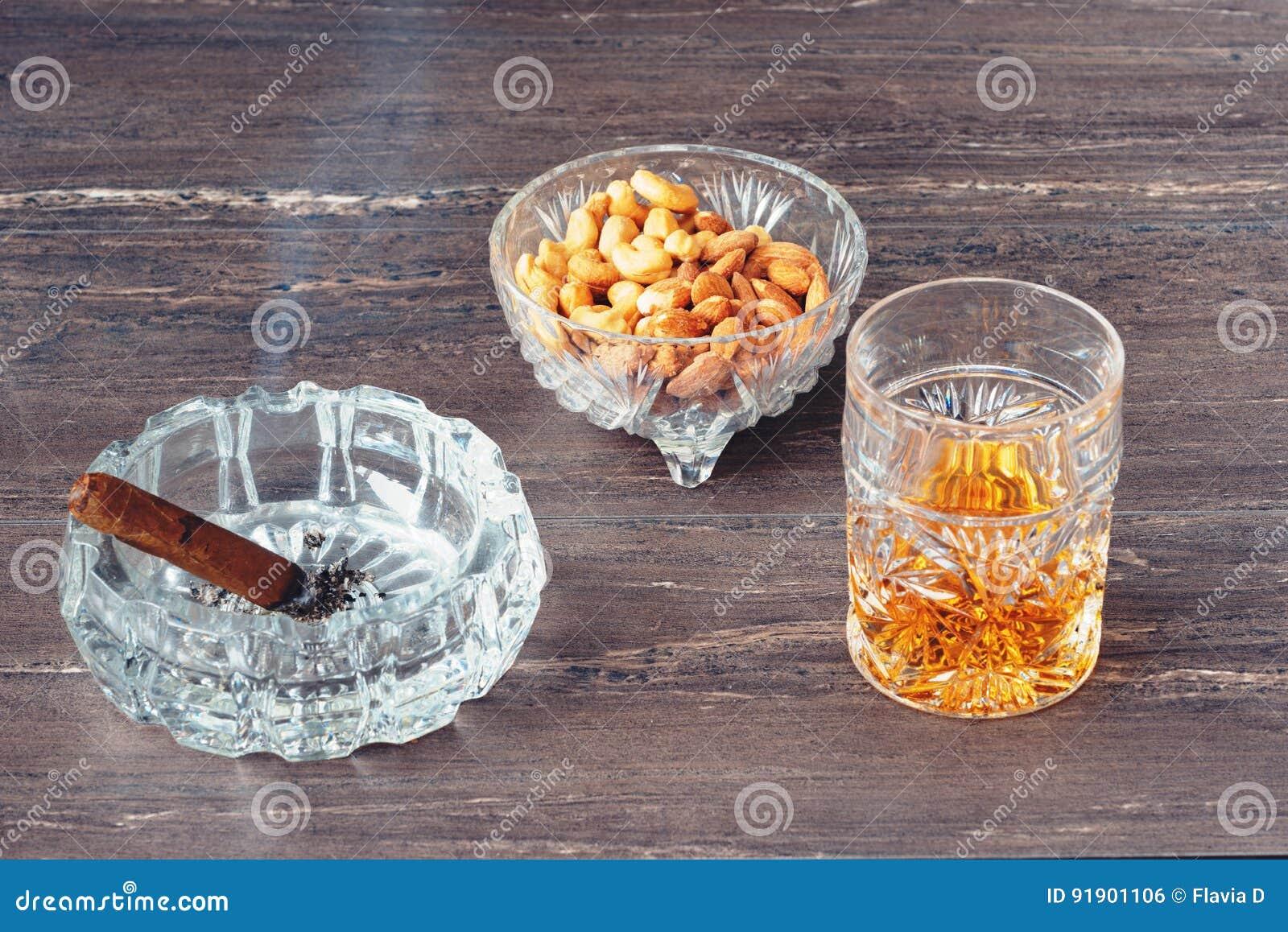 杯威士忌酒、古巴雪茄和坚果在一张灰色木桌上 关闭上色百合软的查阅水