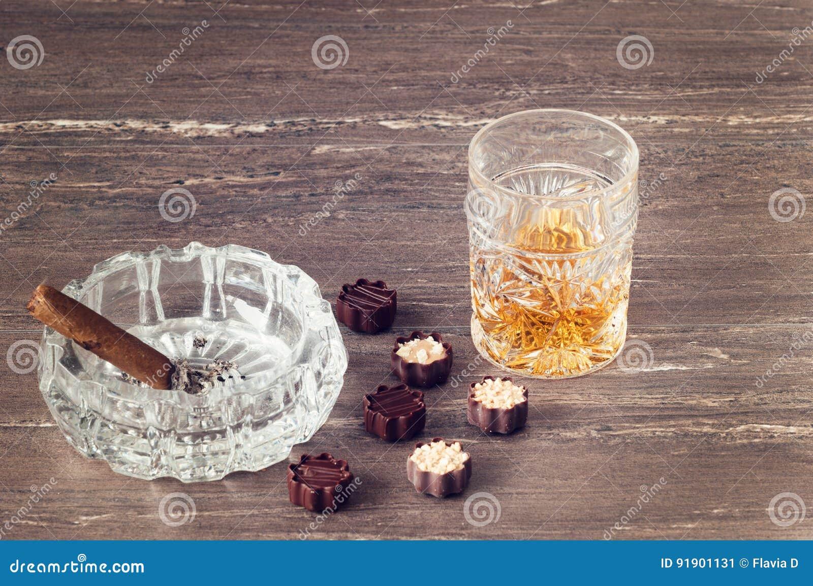 杯威士忌酒、古巴雪茄和巧克力在一张灰色木桌上 关闭上色百合软的查阅水