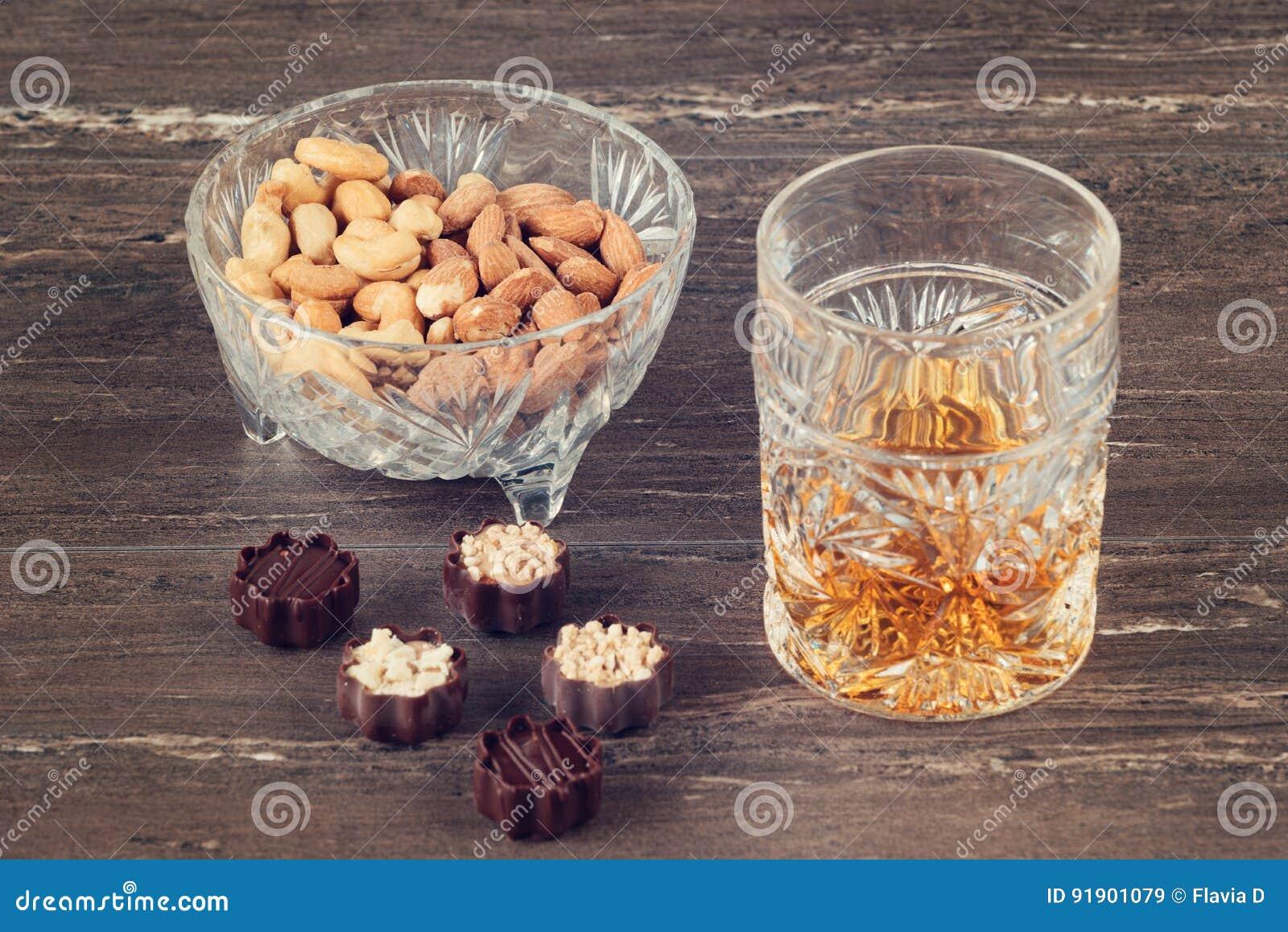 杯威士忌酒、巧克力和坚果在一张灰色木桌上 关闭上色百合软的查阅水