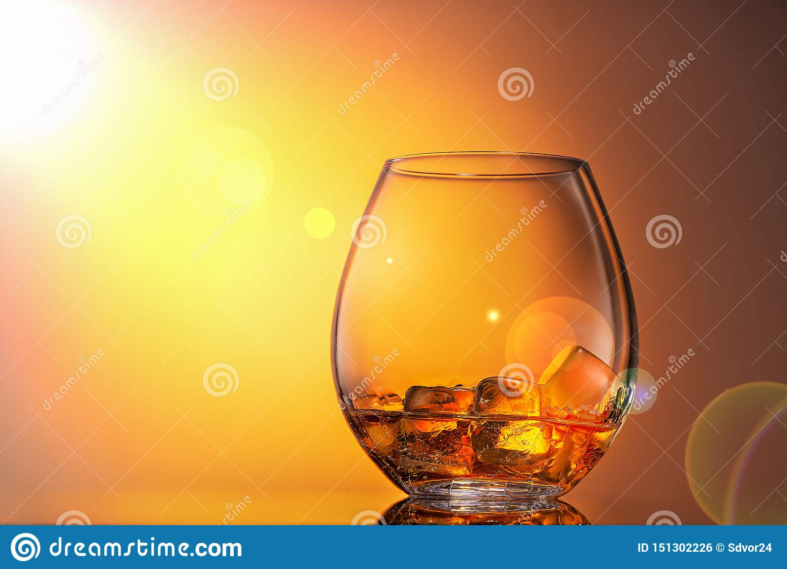 杯威士忌酒刻痕与在橙色背景的冰,它由阳光照亮 o