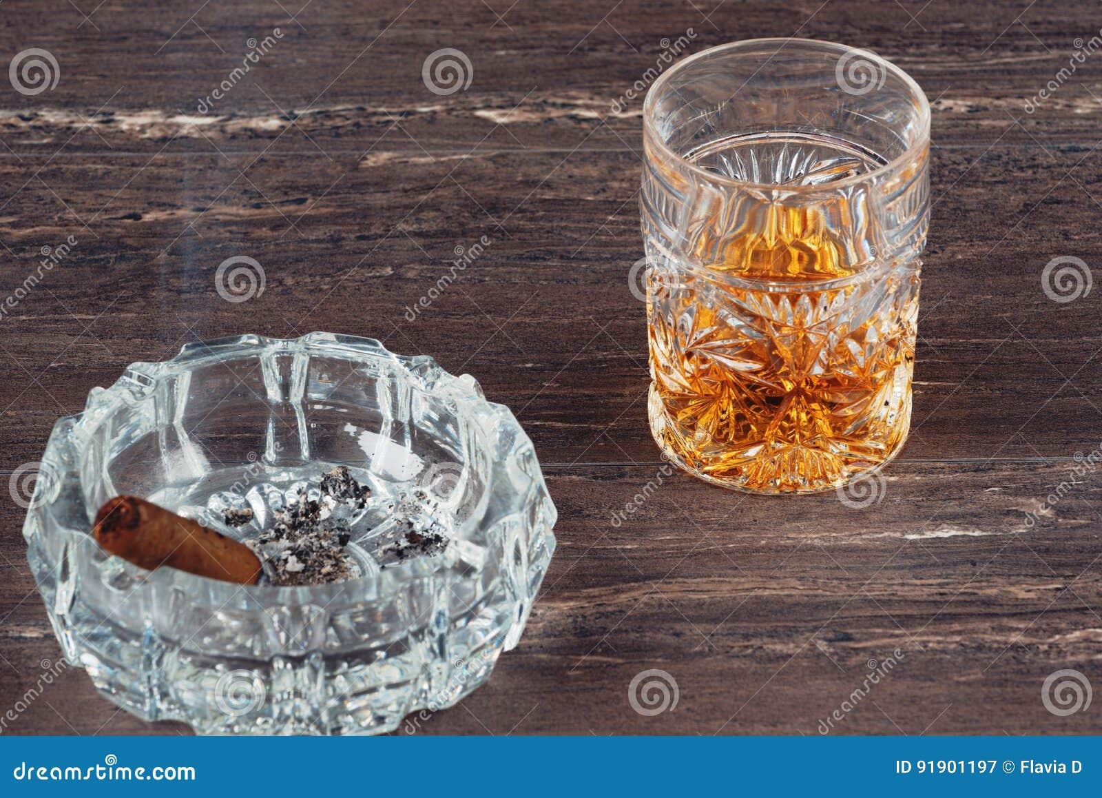 杯威士忌酒和古巴雪茄在一张灰色木桌上 关闭上色百合软的查阅水