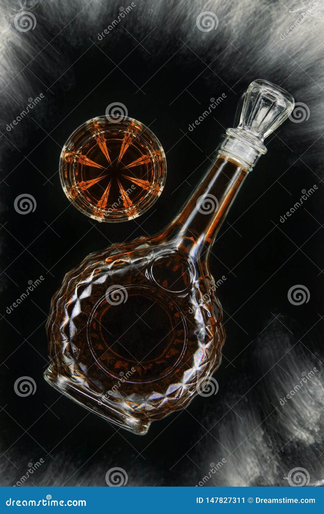 杯威士忌酒或白兰地酒或者科涅克白兰地与玻璃水瓶在被隔绝的黑背景,顶视图