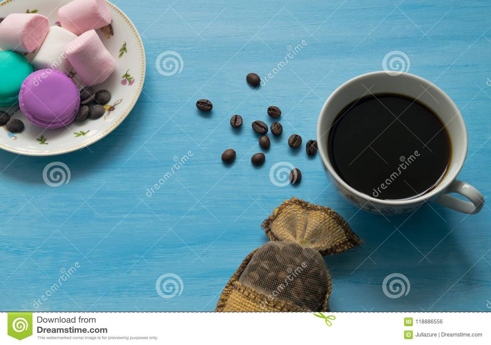 杯热的咖啡用蛋白软糖和蛋白杏仁饼干在蓝色背景