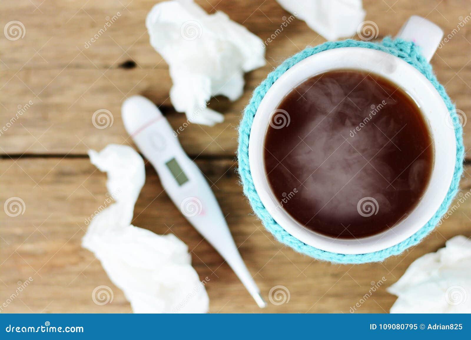 杯热的茶、纸抹和温度计在建议木的桌上流感季节