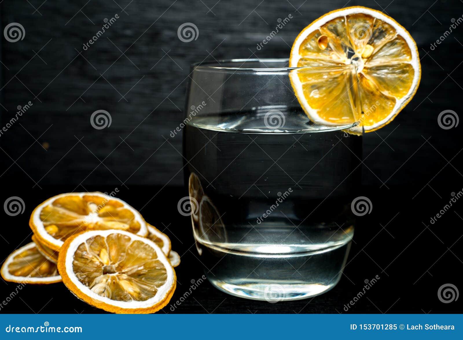 杯的关闭与干柠檬切片的水在后面