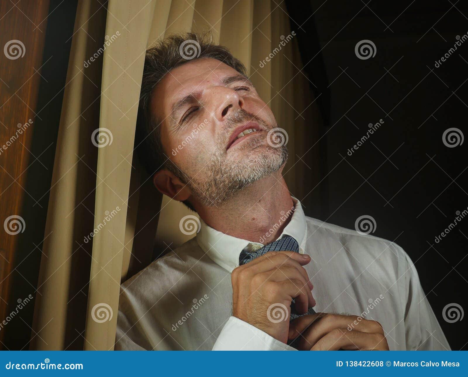 松开领带感觉被挫败的遭受的消沉和问题的年轻哀伤和沮丧的商人倾斜在窗口