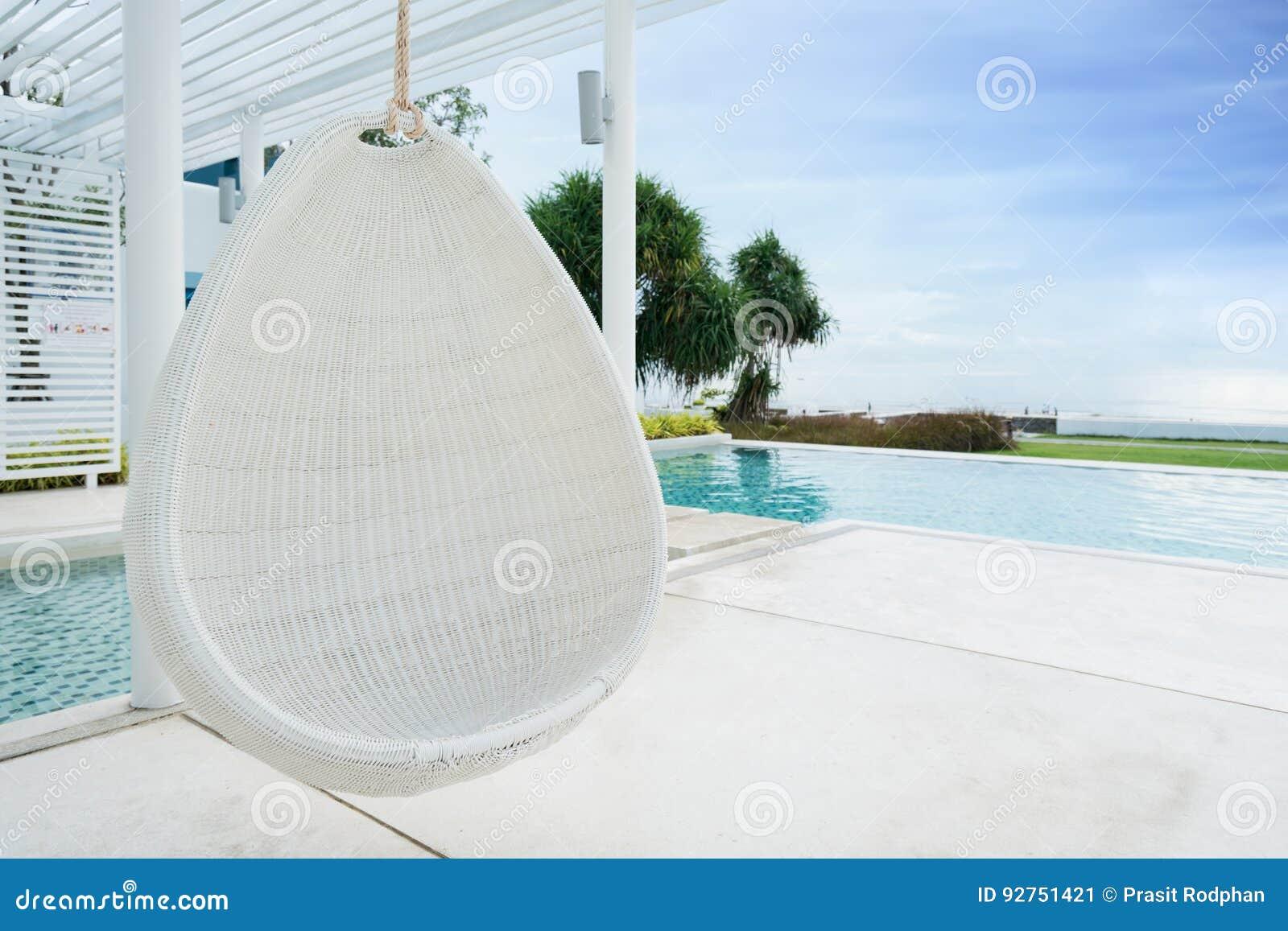 松弛白色在游泳池的藤条垂悬的椅子在海视图