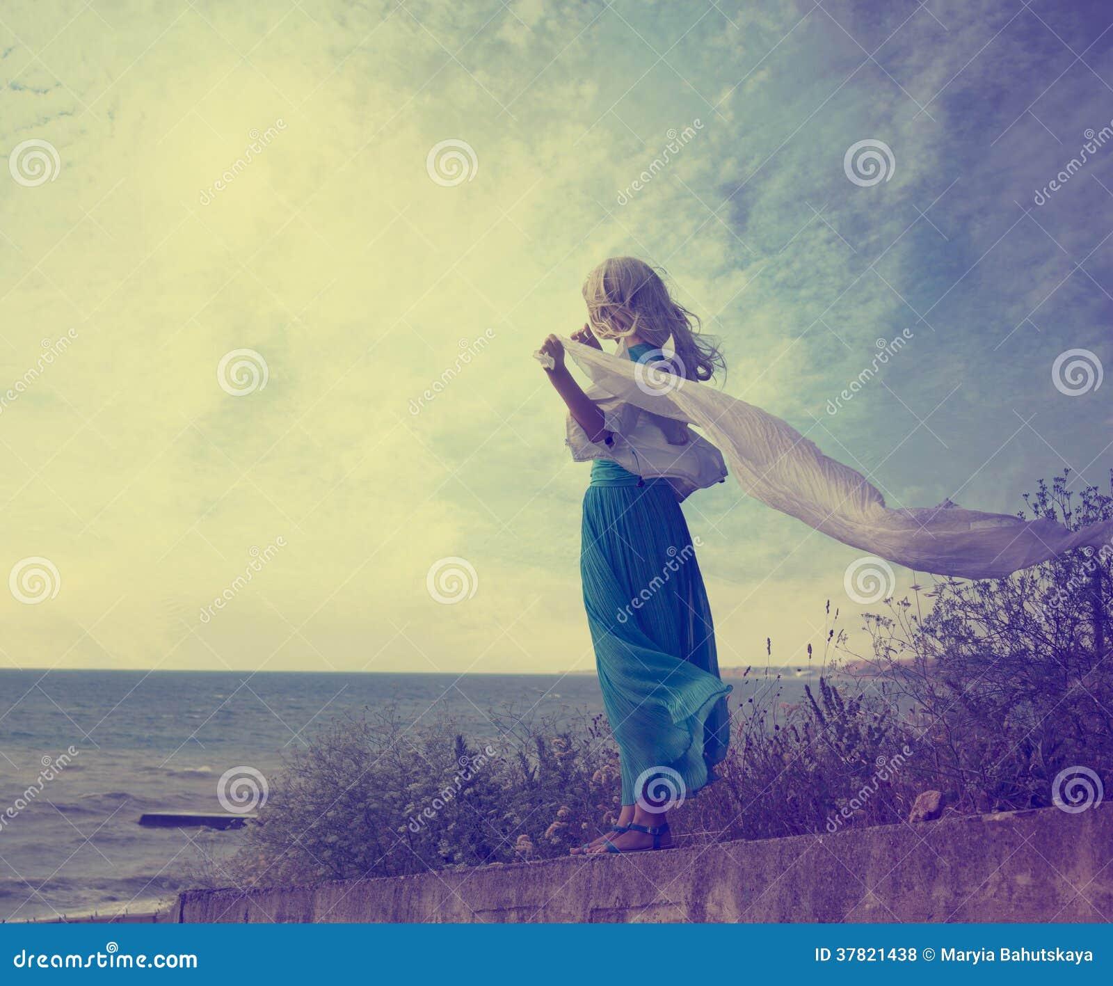 绿松石礼服的孤独的妇女有挥动的围巾的