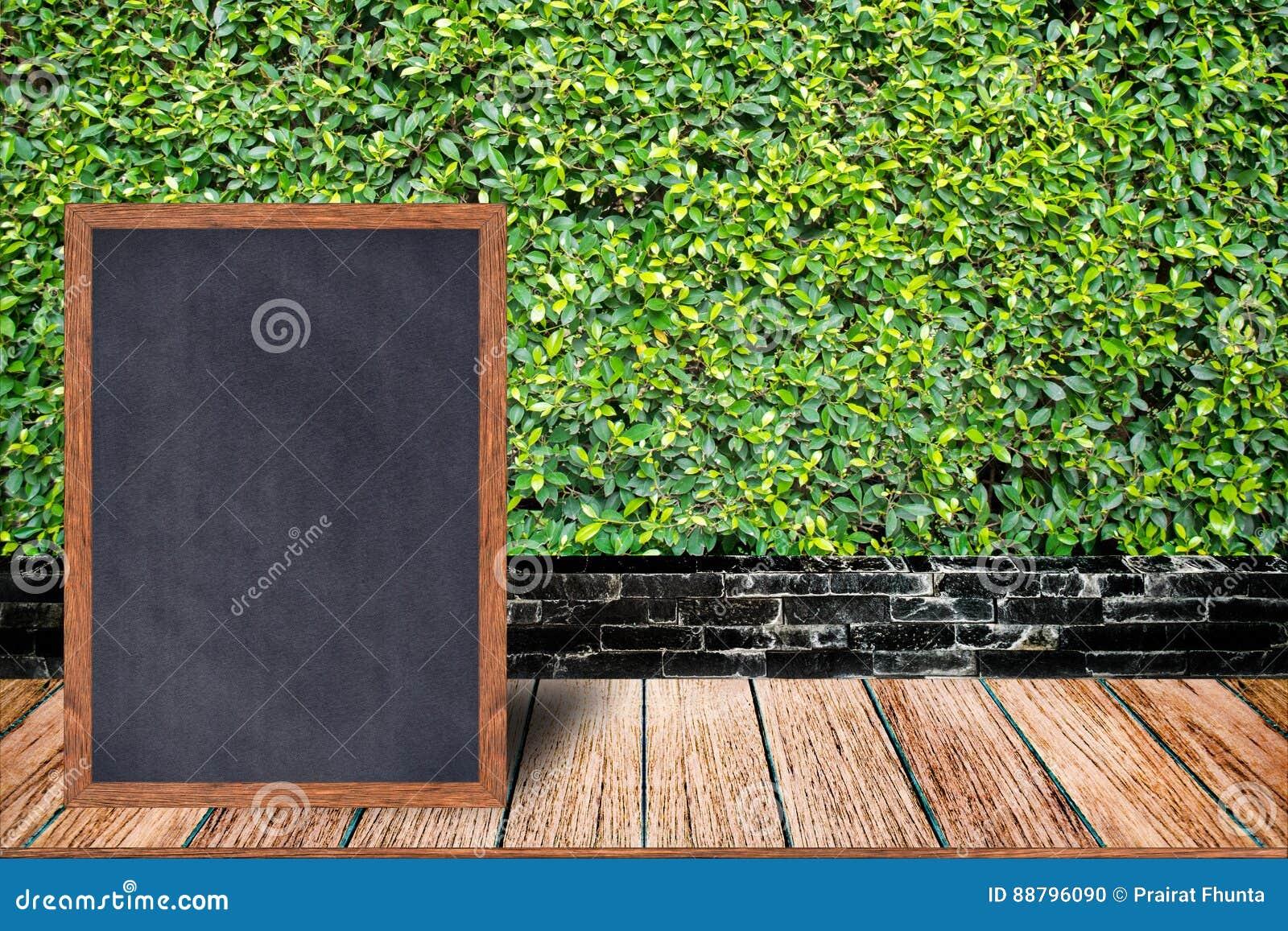黑板木框架、黑板标志菜单在木桌上和草围住背景
