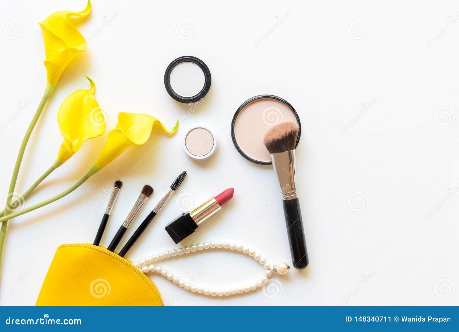 构成化妆用品工具和秀丽化妆用品礼物、产品和面部化妆用品包裹唇膏有黄色花的在白色b