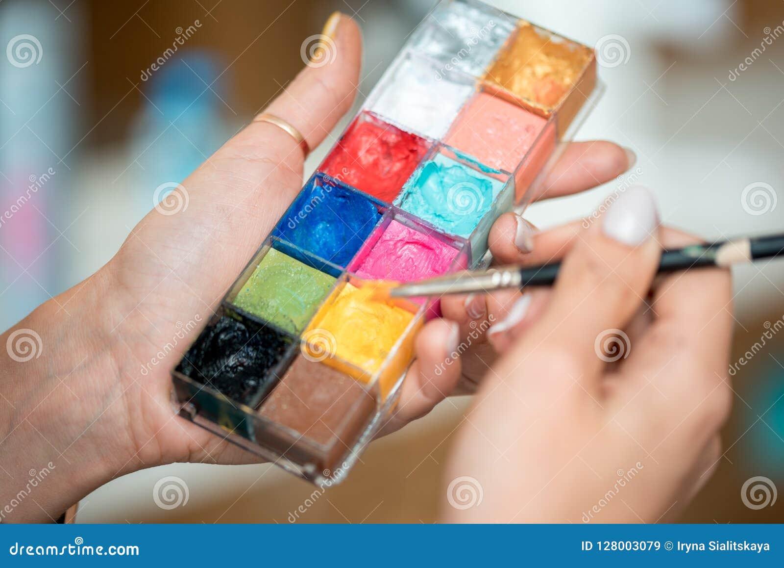 构成调色板?在面孔和人体艺术的化妆师明亮的颜色的手上
