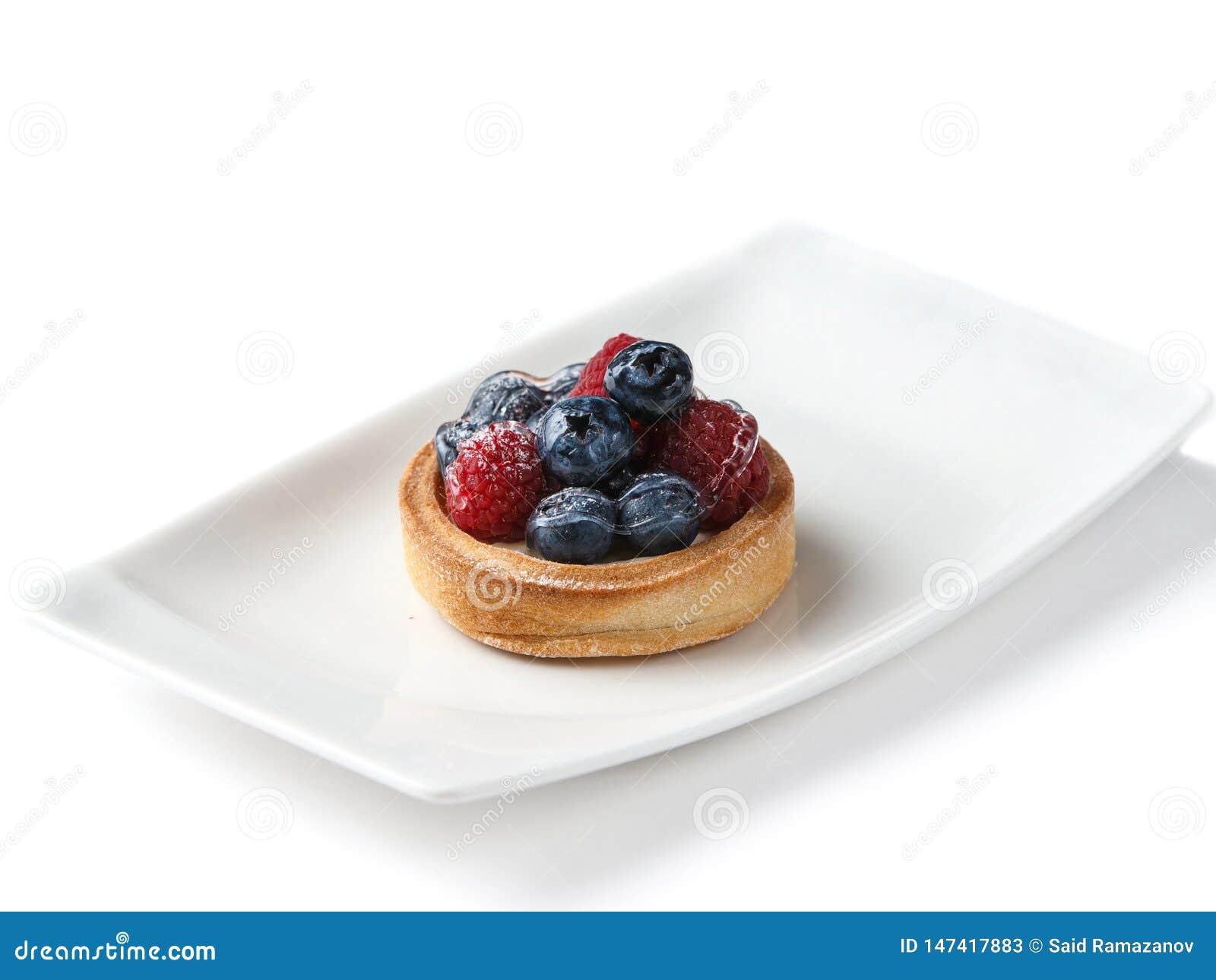 果子馅饼用在一块白色板材的莓果在被隔绝的白色背景