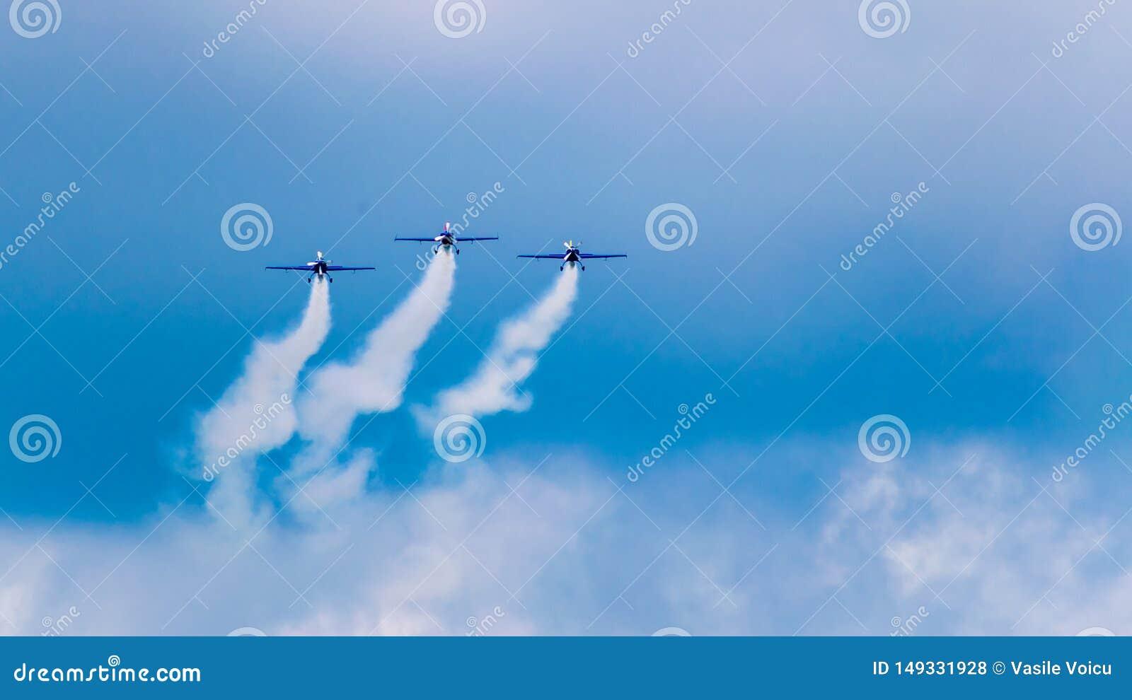 3架表现喷气机,一前一后飞行,在与白色云彩的一天空蔚蓝