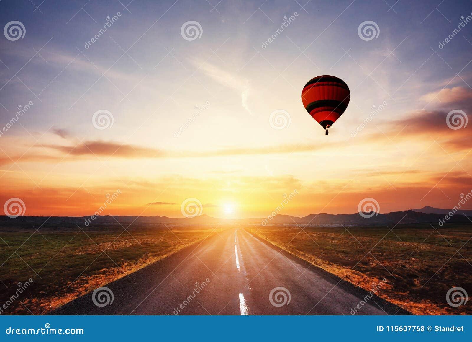 柏油路和在天空的色的球在日落
