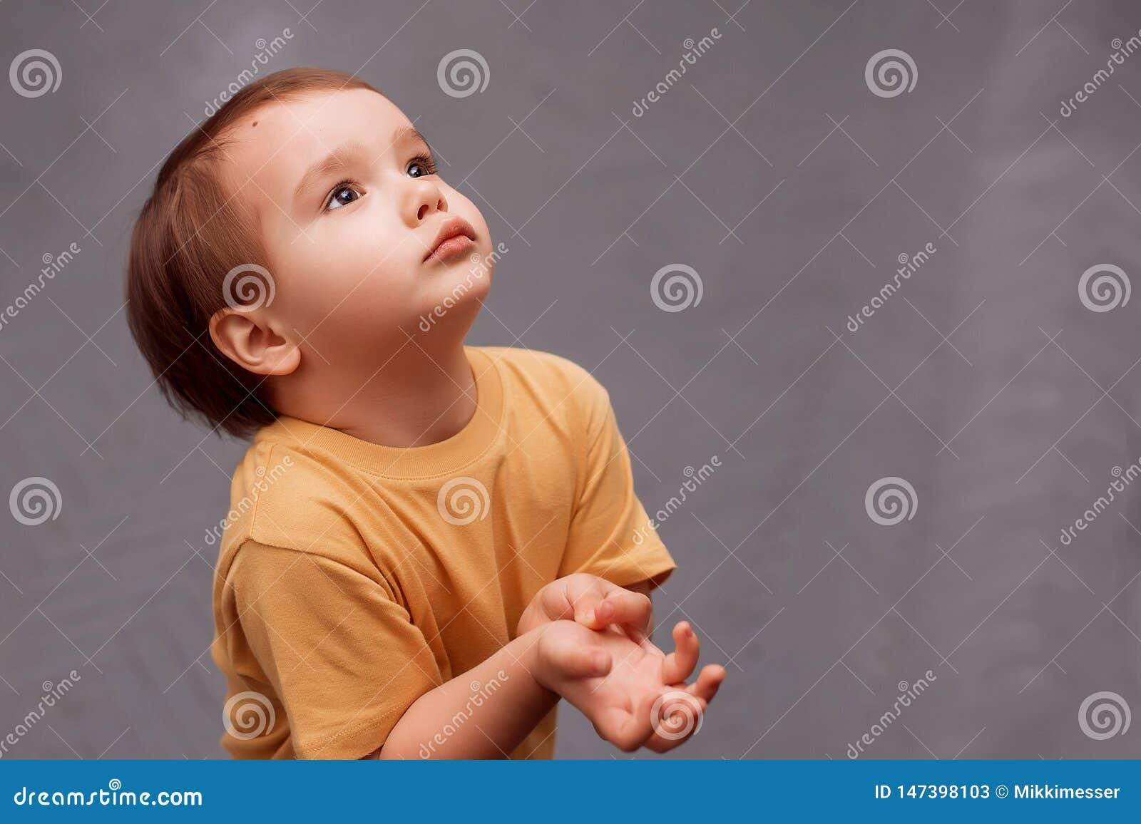 查找黄色的衬衣的小小孩男孩站立和请求某事 孩子握手被举对胸口,如他