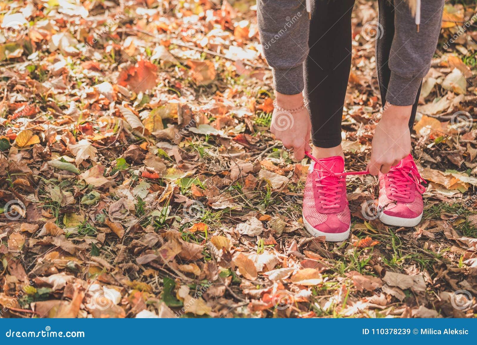 栓在运动鞋的妇女鞋带在训练前