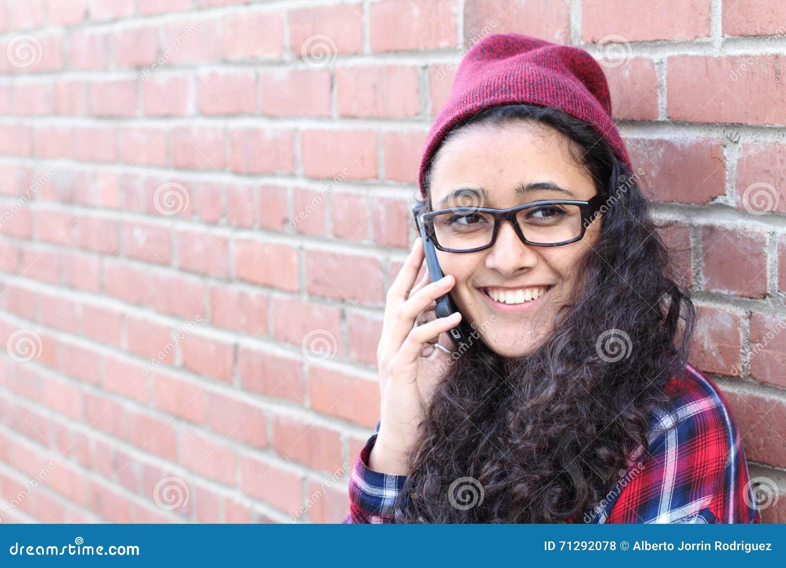 格子花呢上衣和童帽帽子的微笑的冬天行家女孩有在砖墙上的手机的 少年通信概念