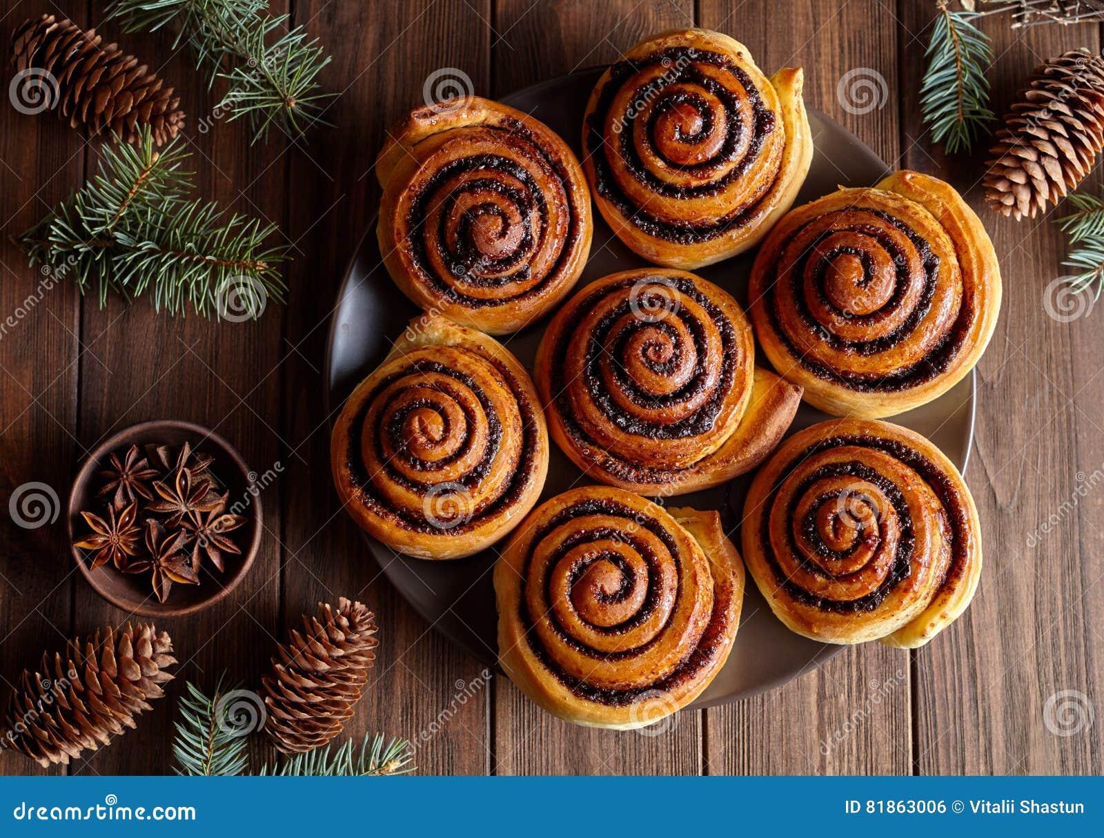 桂皮卷小圆面包在一张木早餐桌上的圣诞节烘烤 顶视图 与杉木锥体的欢乐装饰