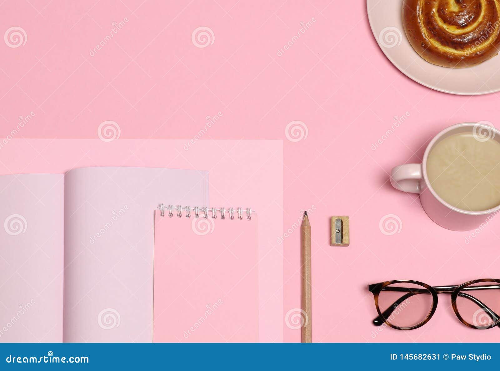 桃红色便条纸,木铅笔,磨削器,咖啡杯,在桃红色背景的蛋糕