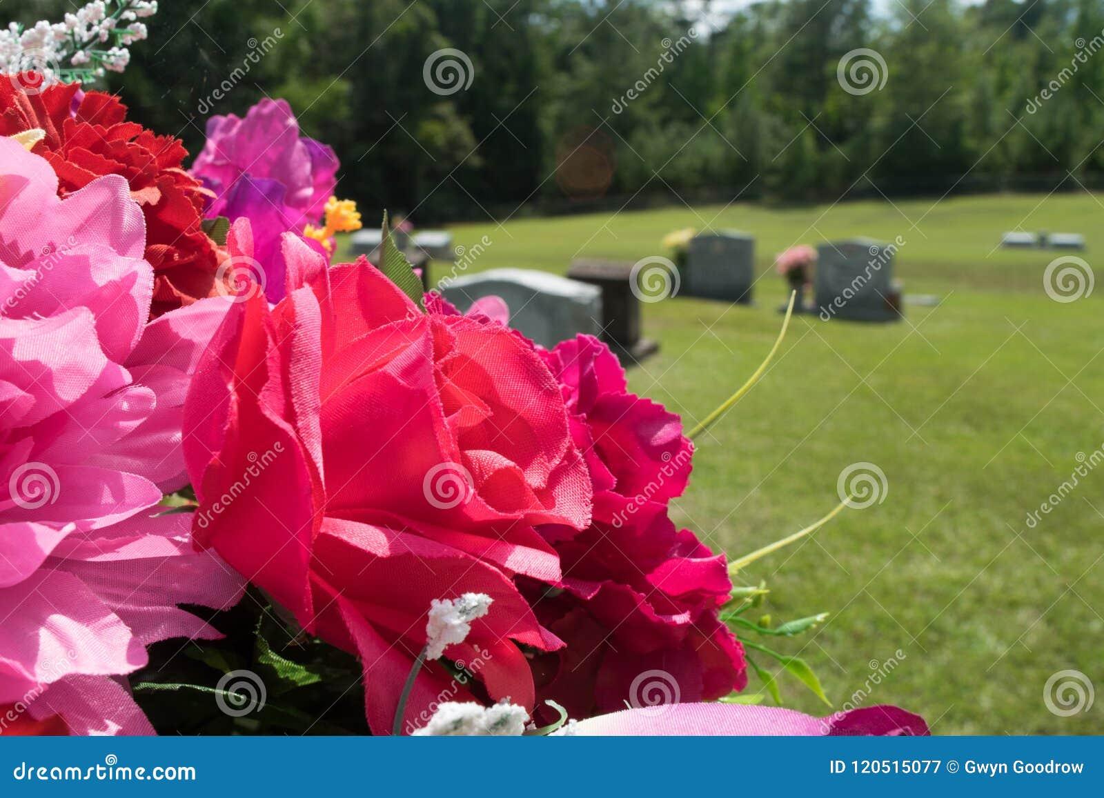 桃红色和红色织品花在公墓