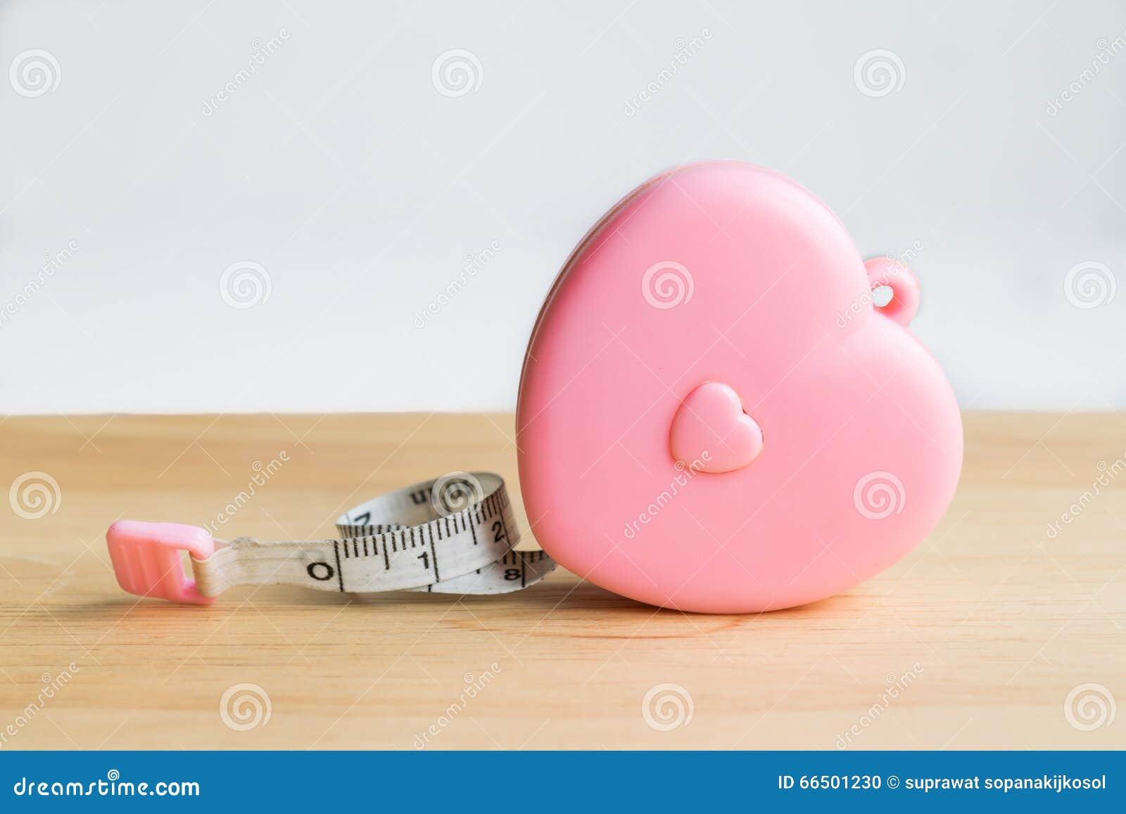 桃红色在木头的心脏测量的磁带