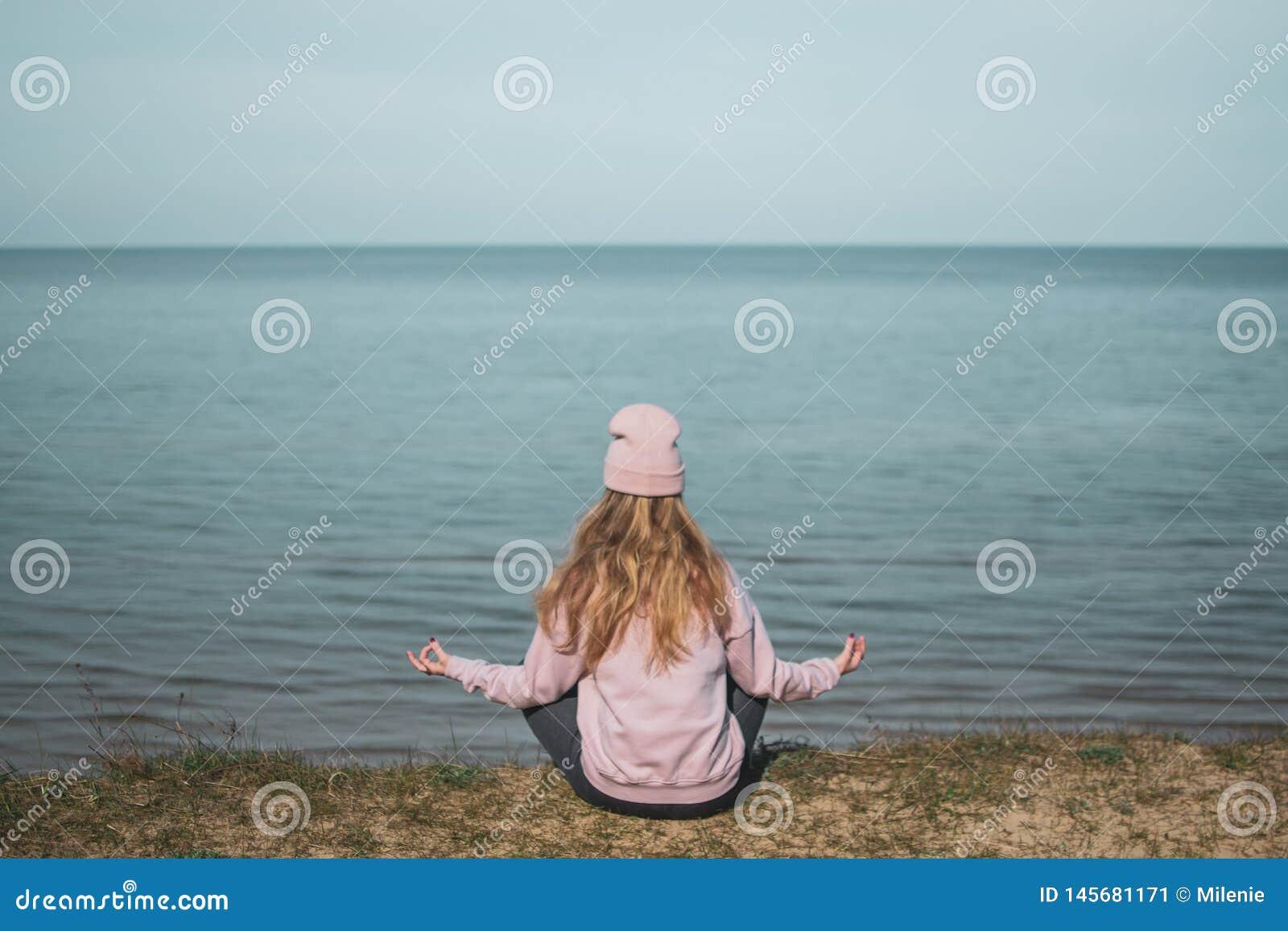 桃红色帽子的年轻妇女单独坐虚张声势,看海,自由概念,平安的大气