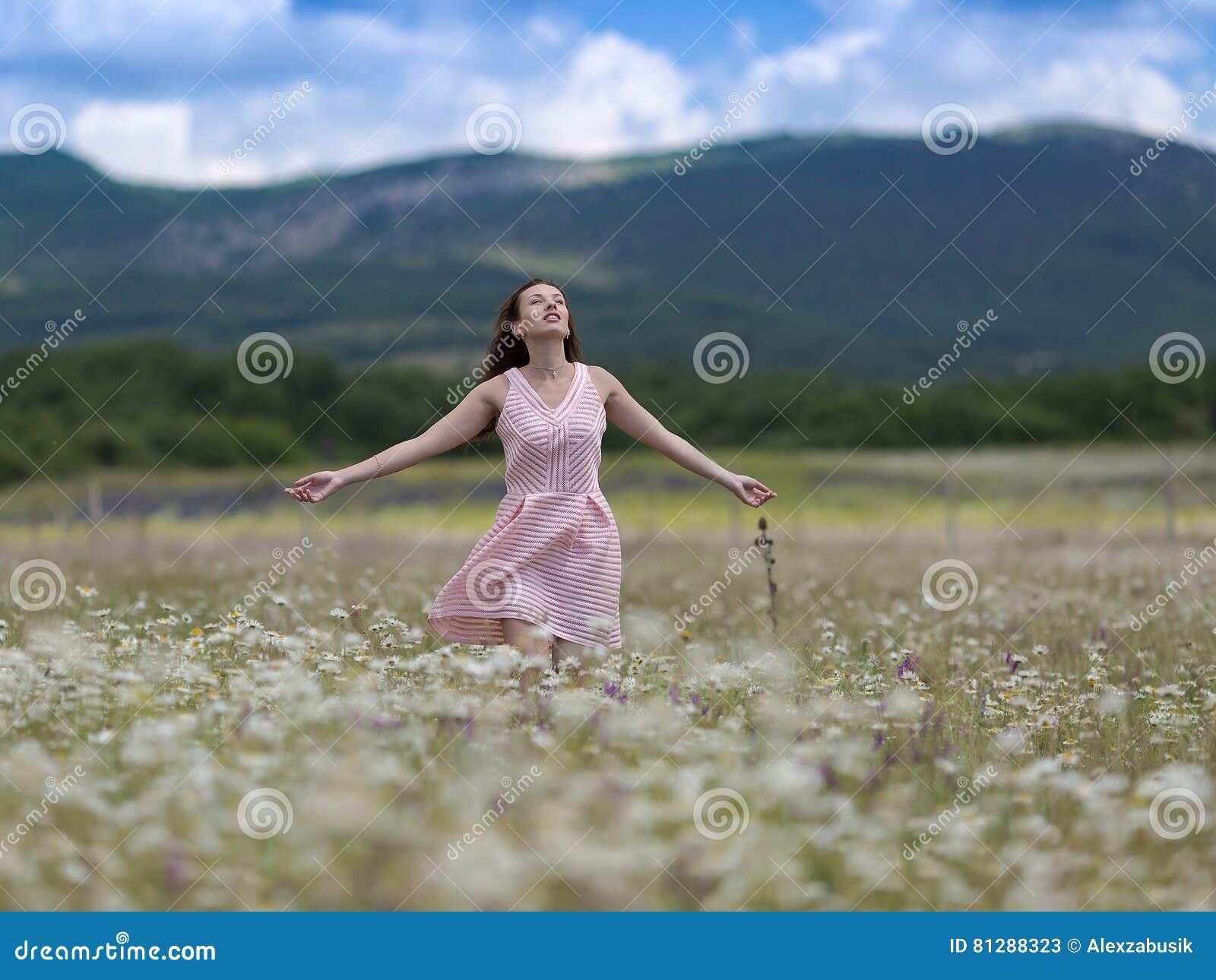 桃红色无袖的礼服的女孩在春黄菊草甸走