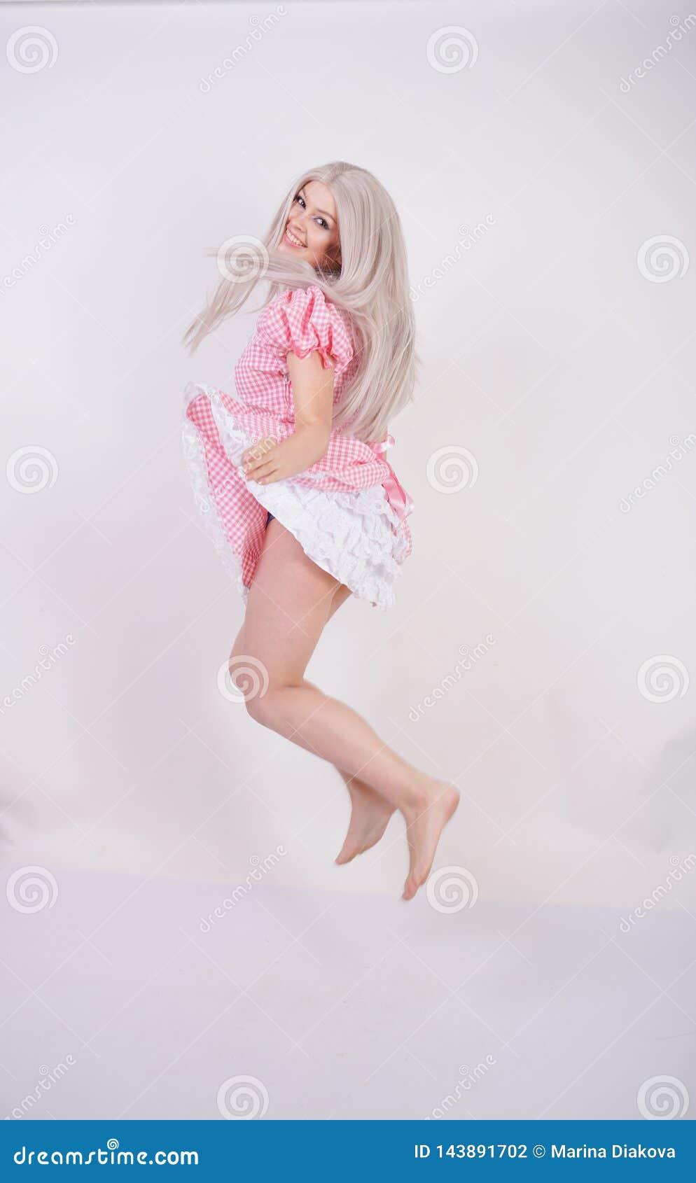 桃红色格子花呢披肩巴法力亚礼服的逗人喜爱的年轻白种人青少年的女孩有摆在白色演播室坚实背景的围裙的