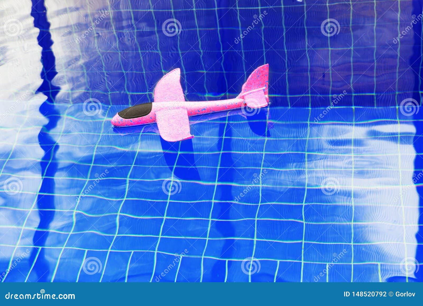 桃红色玩具飞机游泳场没人